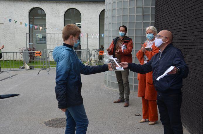 Davidsfondslid Geert reikt de derde prijs uit aan Niels Coppens, leerling van het zesde leerjaar van de Sint-Aloysius Basisschool.