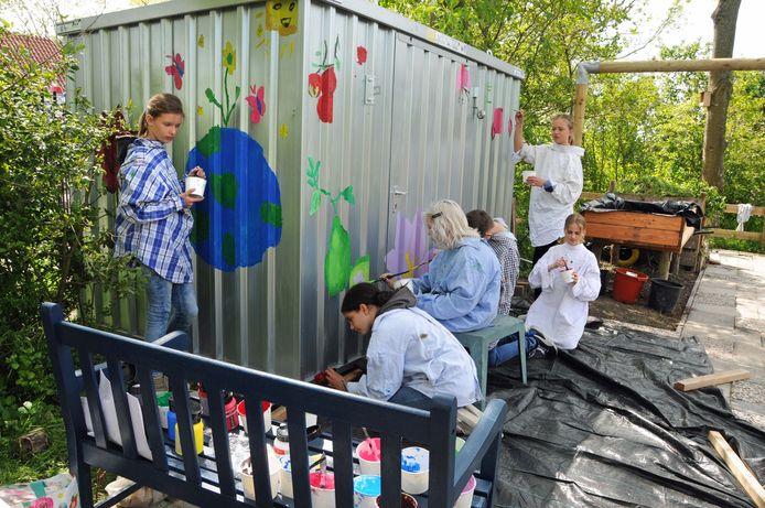 Leerlingen uit groep 7 en 8 van de Jan Wouter van den Doelschool kleuren allerlei figuren in op het nieuwe tuinhuis van Poortambacht. Vlnr Moya, Farida, Demi, Lucas, Silke en Froukje.