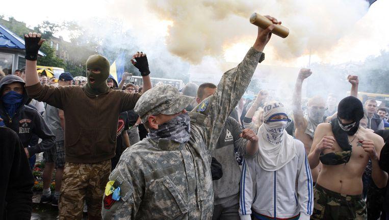 Radicale demonstranten verbranden vlaggen tijdens een protest voor de Russische ambassade in Kiev op zaterdag. Beeld AFP