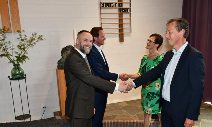 De predikanten en ouderlingen van dienst van de Bethelkerk en Koningskerk in Langerak schudden elkaar de hand bij aanvang van de dankdienst.