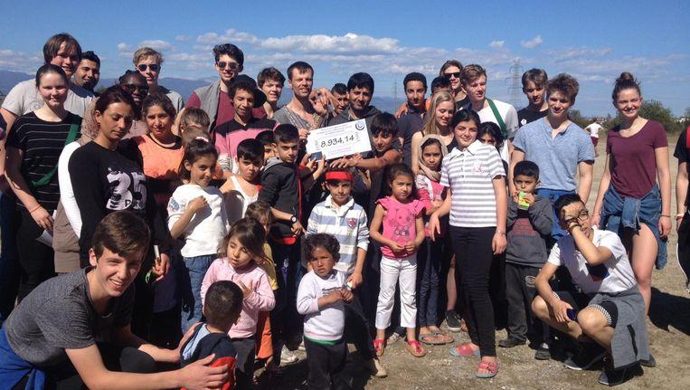 De leerlingen overhandigen zaterdag de cheque bij de vluchtelingenopvang. Beeld Alette Rosing