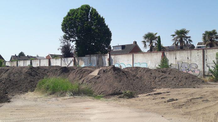 Slechts een muur scheidt de stortplaats van grond aan Laan Hart van Zuid af van de woningen aan de Loweg. Bewoners klagen daar over overlast van stuifzand.
