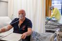 """Cees (71) leest rustig de krant. Hij verblijft nu een week in het ziekenhuis. Hoe het gaat? """"Heel goed. Ik hoop dat ik snel dit kapje af mag."""""""
