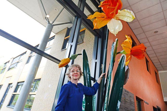 """Kunstenares Linda Nieuwstad bij de narcis die ze schonk aan het Roessingh. """"Mijn bloemen leiden de aandacht even af van de dagelijkse zorgen en brengen wellicht een beetje hoop."""""""