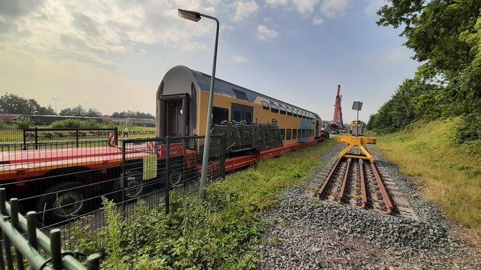 Een oud DDM-rijtuig van de NS wordt in Roosendaal op transport gezet naar de Politieacademie in Ossendrecht.