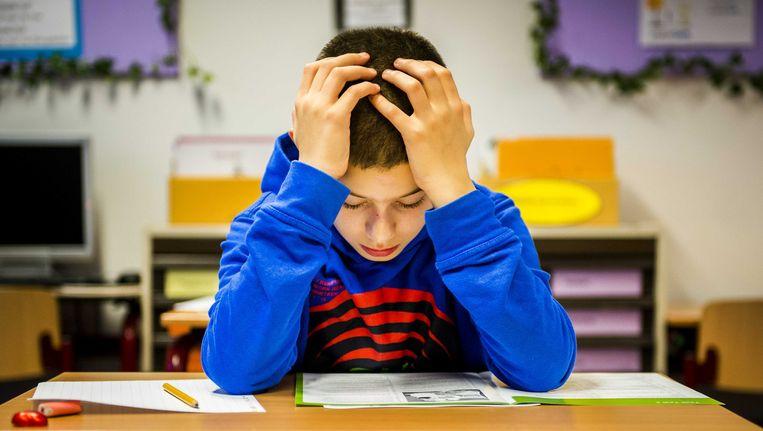 Een leerling buigt zich over de opgaven van de Cito-toets. Beeld anp