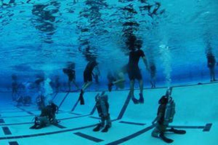 US Navy SEAL's in opleiding in Coronado, Californië. Tijdens de oefening leren de aankomende marinecommando's hoe ze 's nachts hun uitrusting onder water moeten overdragen aan elkaar. Ze dragen maskers die helemaal zwart zijn gemaakt. Beeld US Navy