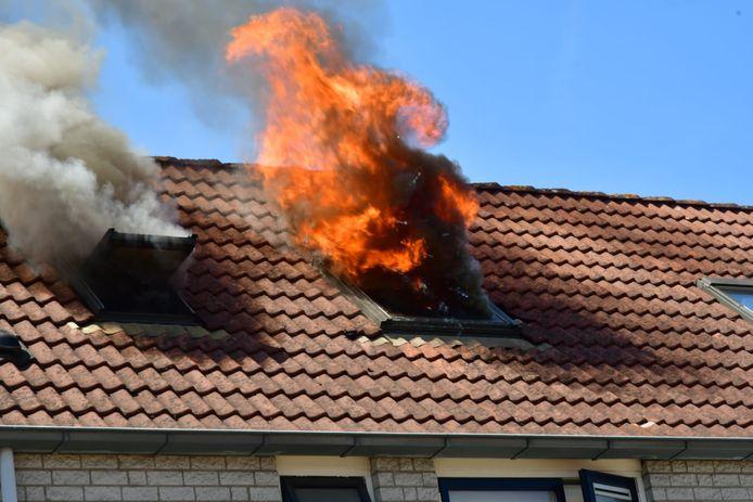 Vlammen slaan uit een dakraam van een woning aan de Korenbloem in Duiven