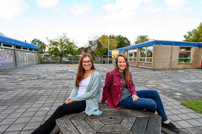 Jorien van Boxel en Amber van Dorst op het nu nog grijze schoolplein, dat groener moet worden.