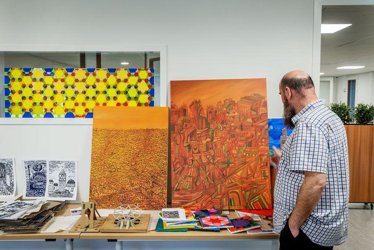 Een docent bekijkt werkstukken van leerlingen van het Cornelis Haga Lyceum. Beeld Jean-Pierre Jans