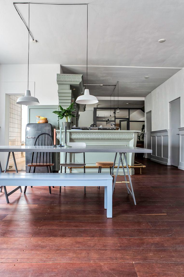 De originele, donkerbruine houten plankenvloer is, samen met de bar, een overblijfsel van het café dat hier ooit huisde. Beeld Henny van Belkom