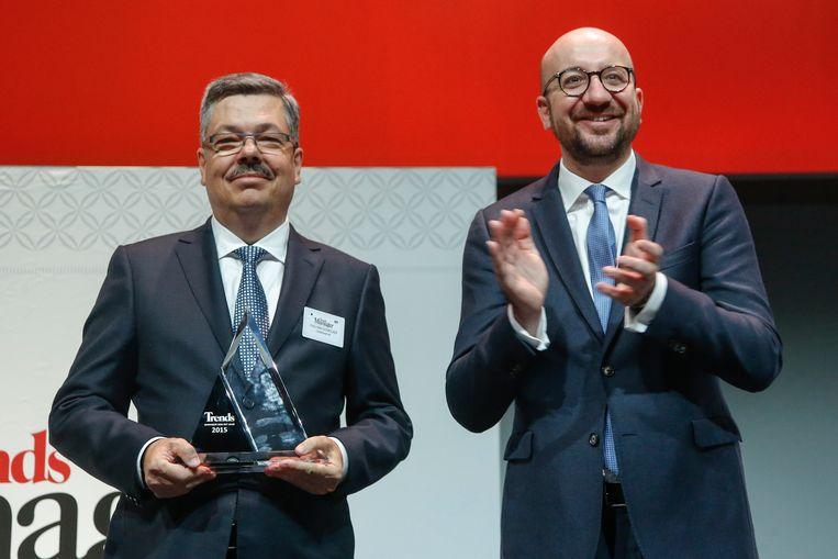 Cartamundi-CEO Chris Van Doorslaer neemt zijn prijs van Manager van het Jaar in ontvangst uit de handen van premier Michel. Beeld BELGA