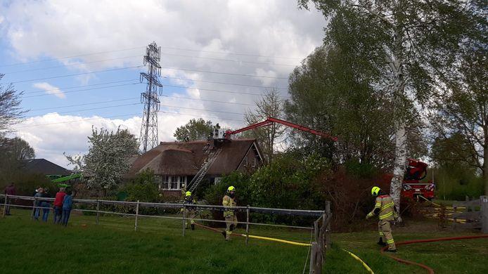 Brandweer is bezig met het blussen van de brand in het rieten dak van een woonboerderij in Didam.