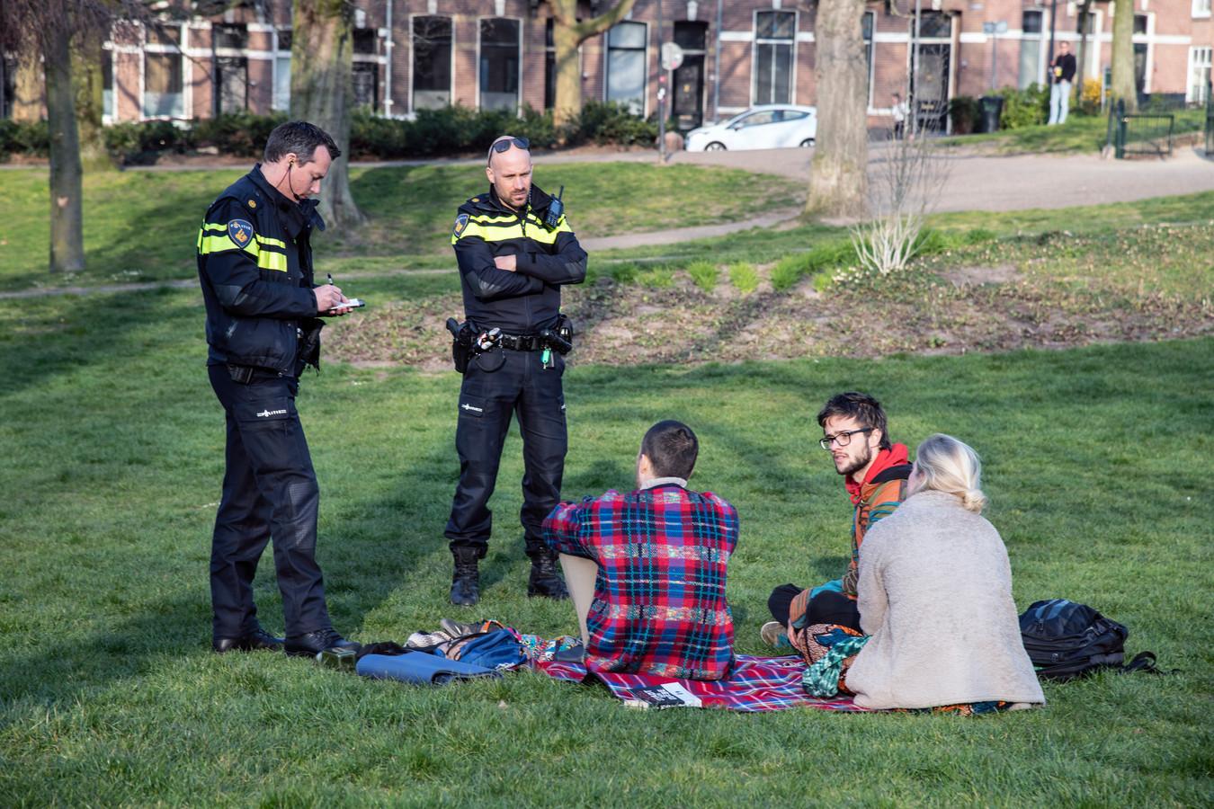 Agenten schrijven een boete uit aan jongeren in een park in Nijmegen.