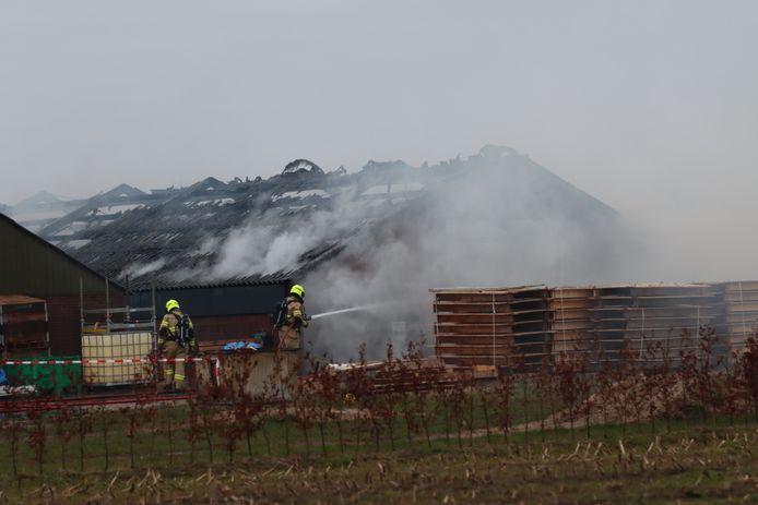 De brandweer bestrijdt het vuur in een schuur aan de Apeldoornseweg bij Otterlo.