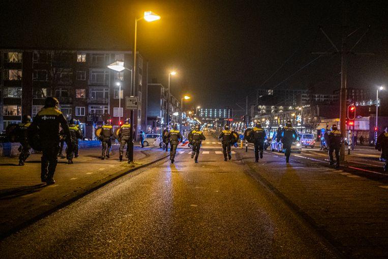 De politie treedt dinsdagavond in Amsterdam-Osdorp tegen jongeren die zwaar vuurwerk afsteken. Beeld Joris van Gennip