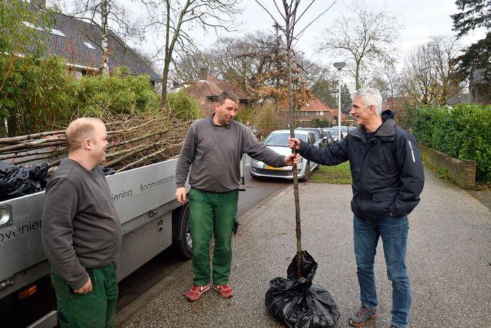 Mark Starink neemt een prunus in ontvangst van Berry van Amersfoort, die met collega Tim Strunk de bomen uitdeelt.