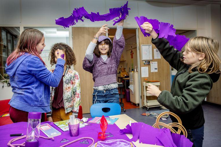 Heleni (11), Nina (9), Yasana (10) en Tiemen (10). De leerlingen van Montessorischool De Amstel versieren de school met paarse slingers.  Beeld Jean-pierre Jans
