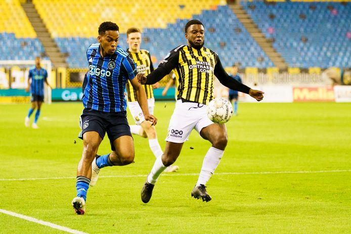 Voetbal voor lege tribunes in GelreDome. Ajaxcied Jurrien Timber  in duel met Vitessenaar Riechedly Bazoer.