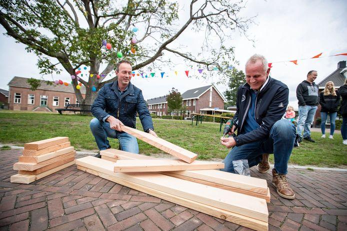 Burendag in Eibergen. Paul de Vries (links) en Jan Kroek helpen een bankje in elkaar te schroeven.