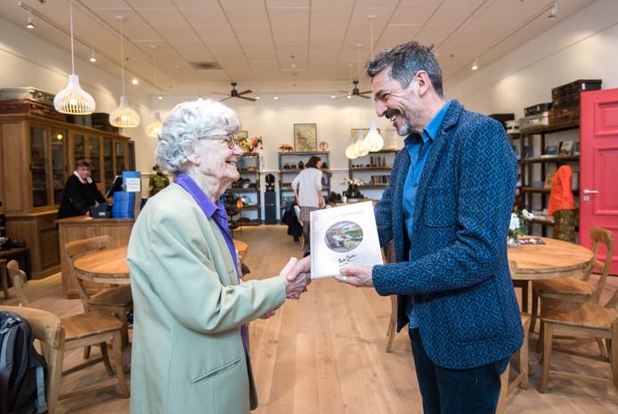 Curator Hans van den Akker van Museum Bronbeek overhandigt het eerste exemplaar van de Indonesische vertaling  het dagboek 'Lieve Gerda' aan Gerda Peeters.