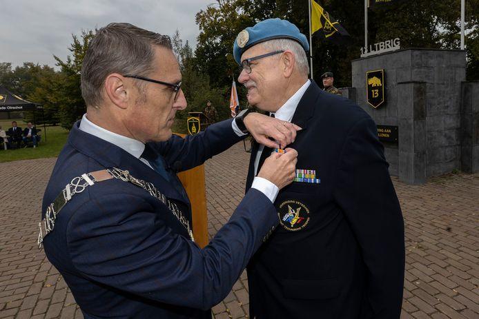 Burgemeester Frank van der Meijden van Laarbeek speldt de onderscheiding op.