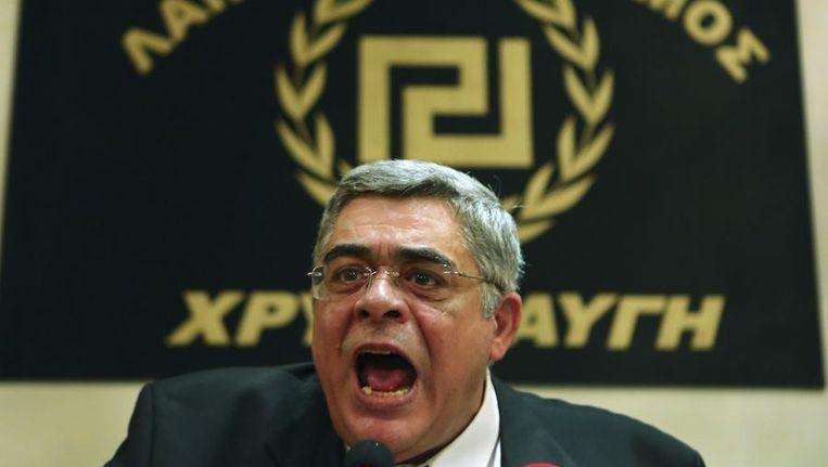 Nikolaos Mihaloliakos spreekt met het partijsymbool op de achtergrond. Beeld null