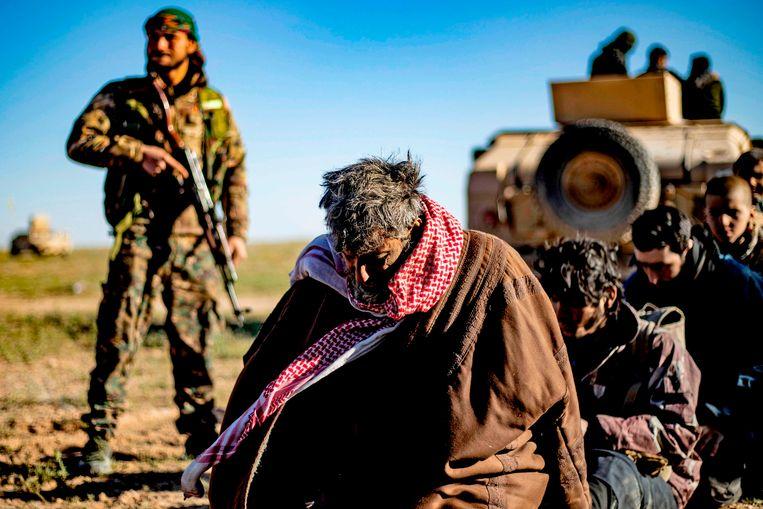 Mannen en jongens die er van verdacht worden IS-strijders te zijn worden gecontroleerd. Beeld AFP