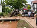 Hulpverleners takelen een auto uit een riviertje dat  buiten de oevers was getreden. Foto Ulf Hürtgen
