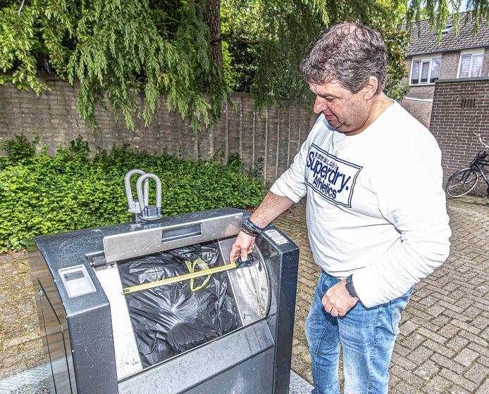 Zwollenaar Tom Voulon meet de invoerbak bij de ondergrondse container aan de Westenbergmate.