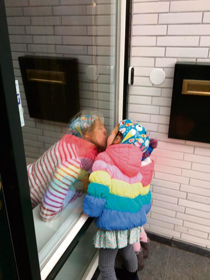 Oma en kleindochter kussen met een ruit ertussen.