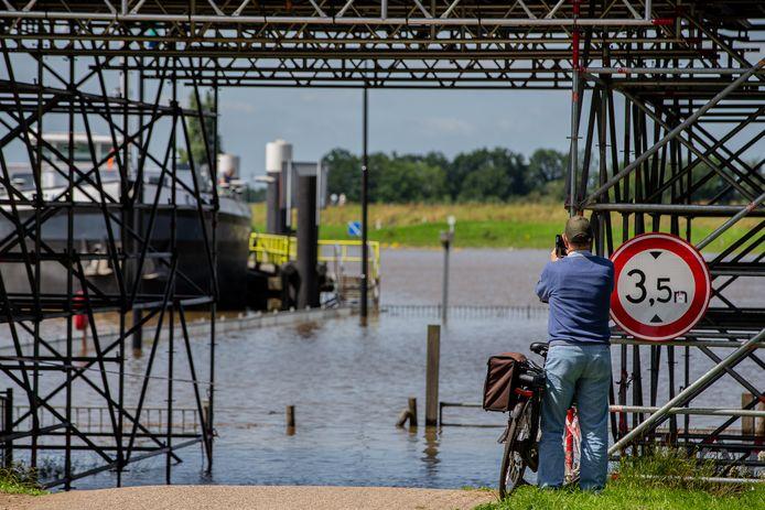 Hoogwater bij de brug van Grave trekt het nodige hoogwatertoerisme .