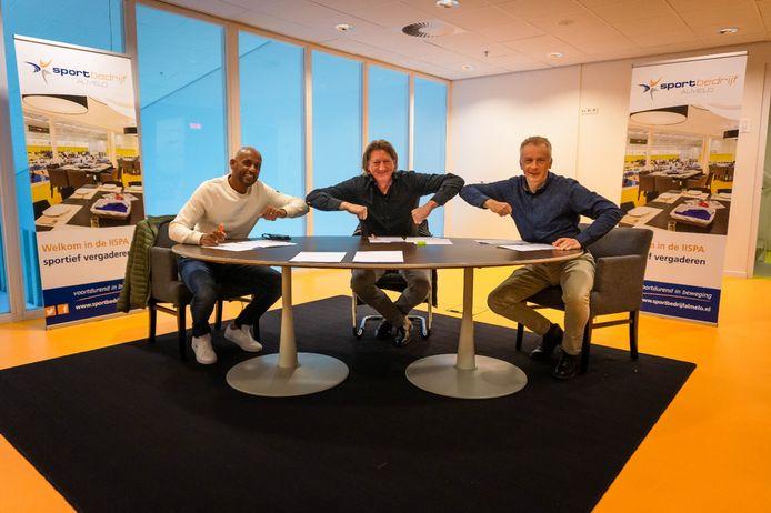 De voorzitters Marco Mahangoe (Almelo FC) en Klaas Geert Bakker (Uitsmijters) en directeur Gerwin Pol van het Sportbedrijf (vlnr) tekenen het contract in de IISPA