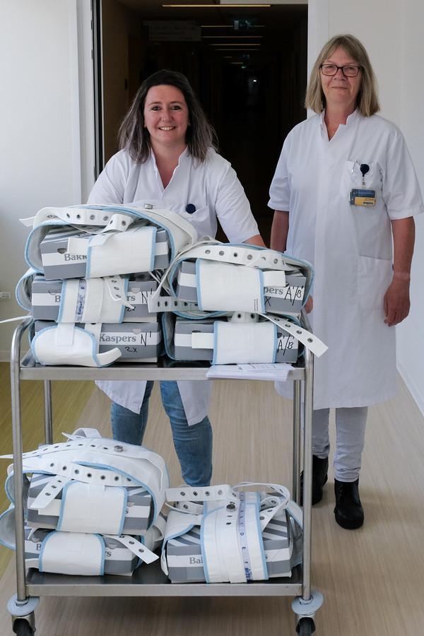 Janneke de Laak (l.) en Aleid Rhebergen brengen taart rond op de verpleegafdelingen met de gewraakte fixeerbanden om de taartdozen om te vieren dat de banden zijn weggehaald.