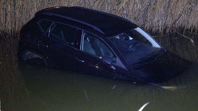 De donkere auto is in het water terecht gekomen.
