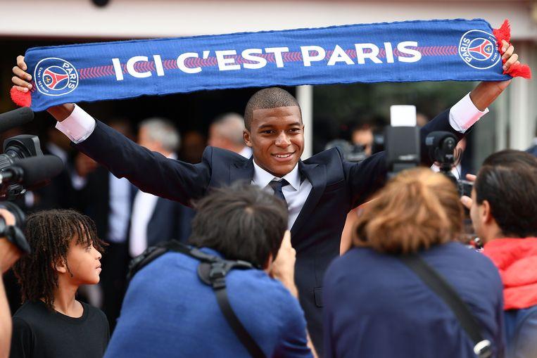 In 2017 tekent Kylian Mbappé bij Paris Saint-Germain. Zijn broertje Ethan (l) kijkt bewonderend toe. Beeld AFP
