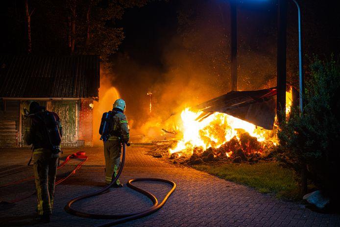 De brandweer probeert de brand in een volledige afgebrande schuur onder controle te krijgen.