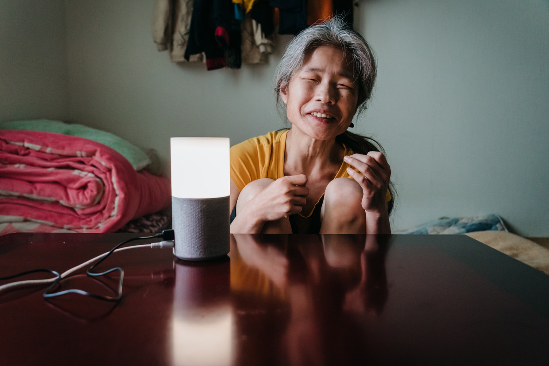 De bijna volledig blinde Jang Ae-ja (55) met de slimme speaker in haar huis in Seoul. Beeld Jun Michael Park