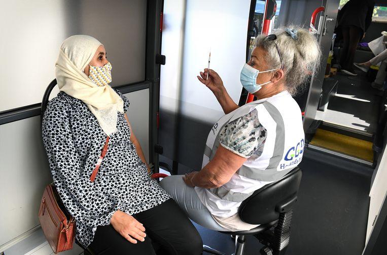 Een vrouw heeft besloten zich alsnog te laten inenten in de prikbus in Leiden tegenover de moskee. Beeld Marcel van den Bergh / de Volkskrant