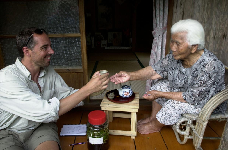 Dan Buettner bij een eeuwelinge in Okinawa Beeld DAVID MCLAIN