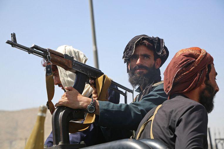 Taliban-strijders houden de wacht in een voertuig langs de kant van de weg in Kaboel op 16 augustus 2021, na een verbluffend snel einde aan de 20-jarige oorlog in Afghanistan, terwijl duizenden mensen de luchthaven van de stad bestormden en probeerden te vluchten.  Beeld AFP