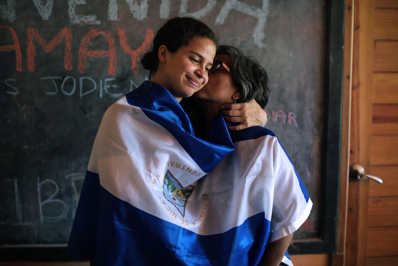 Activiste Amaya Coppens krijgt een kus van haar moeder. 'Er zijn dit jaar in Nicaragua wellicht meer mensen gestorven door Ortega dan door covid.' Beeld AFP
