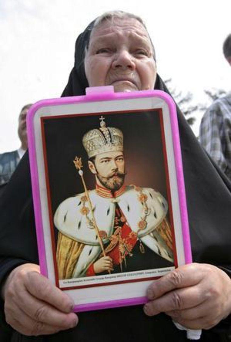 Een vrouw in Moskou met een portret van tsaar Nicolaas II in juli 2008, tijdens een herdenking van de executie van de koninklijke familie. Beeld EPA