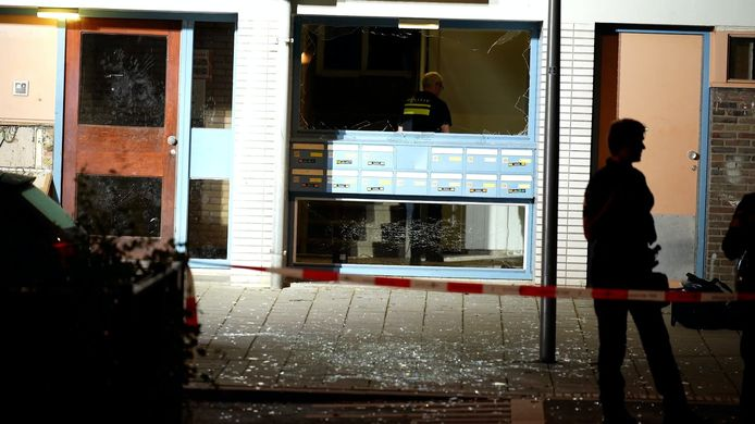 Glasscherven op straat en een gebroken ruit, na de explosie aan de Alexander de Grotelaan in de Utrechtse wijk Kanaleneiland.