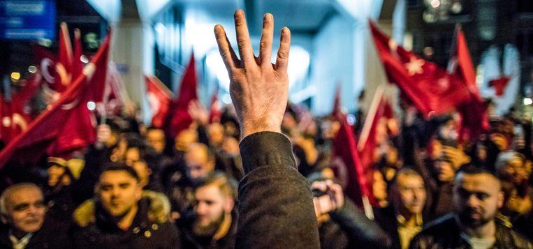 Een demonstrant in Rotterdam maakt het 'Rabia-figuur' als blijk van steun aan Turkse president Erdogan. Beeld Freek van den Bergh / de Volkskrant