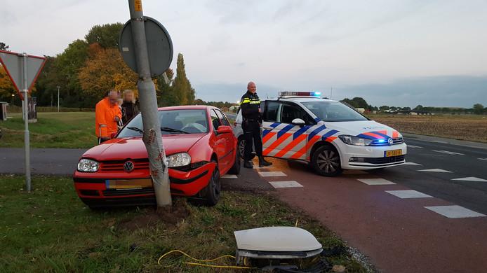 De rode auto schoot na de kop-staartbotsing tegen een lantaarnpaal aan.