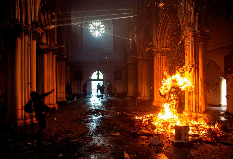 Demonstranten in een brandende kerk in Santiago op de eerste verjaardag van de sociale oproer in Chili, 18 oktober 2020.  Beeld AFP