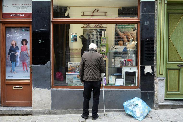 Een man kijkt naar de etalage van een gesloten winkel in Brussel.  Beeld REUTERS