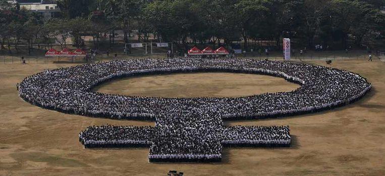 Duizenden Filipijnen vormen een gigantisch vrouwensymbool in hoofdstad Manilla. Beeld null