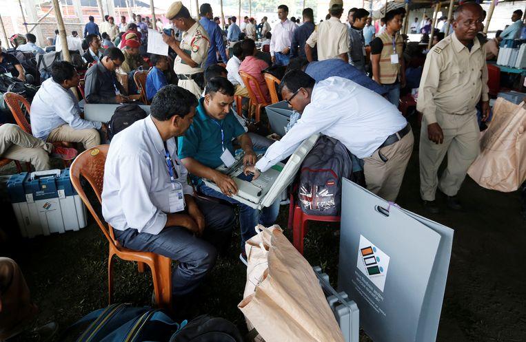 Ambtenaren controleren de stemcomputers in Majuli, in het noordoosten van India.  Beeld REUTERS